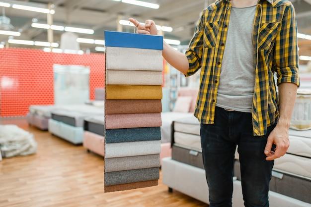 젊은 남성 사람은 가구 매장 쇼룸에서 매트리스의 텍스처 팔레트를 보유하고 있습니다. 상점에서 침실에 대한 샘플을 찾는 남자, 남편이 현대 가정 인테리어 용품을 구입합니다.