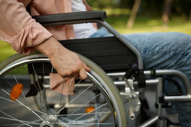 Молодой человек мужского пола в инвалидной коляске. парализованные люди и инвалидность, преодоление инвалидности. человек-инвалид гуляет в парке в солнечный день