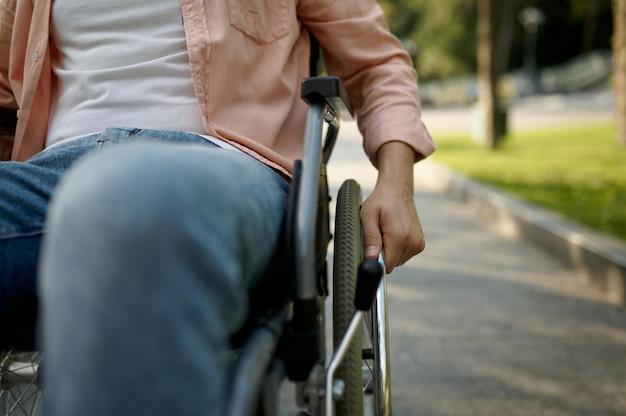 車椅子の若い男性。麻痺した人と障害、ハンディキャップの克服。晴れた日に公園を歩く障害者