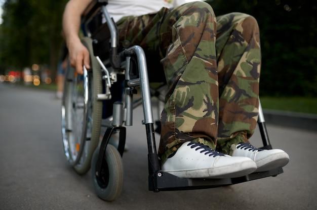 Молодой человек мужского пола в инвалидной коляске, вид на ноги
