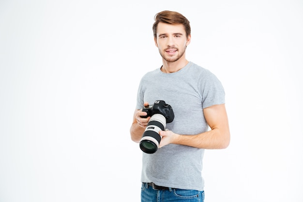 흰색 배경에 고립 된 사진 카메라를 들고 젊은 남성 사진 작가