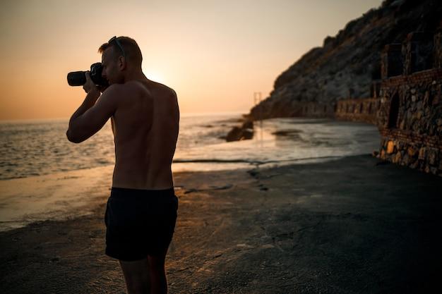 젊은 남성 사진 작가는 해안에 서 있는 동안 해질녘 바다의 사진을 만듭니다. 바다 일몰입니다. 선택적 초점입니다. 관광객 사진 바다 경치