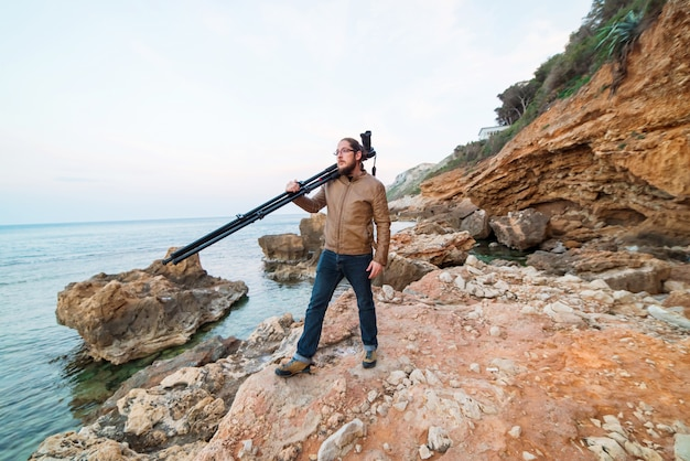 Young male photographer standing on rock with camera on tripod and looking into the sea