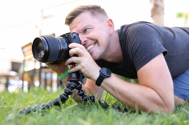 Young male photographer takes pictures on tripod in street profession photographer concept