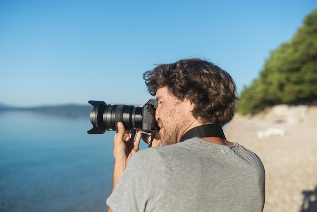 Young male photographer taking photos of beautiful sea and nature in early morning with his professional dslr camera.