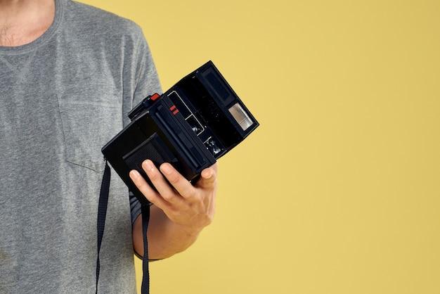彼の手で感情的なポーズの古いフィルムカメラで若い男性カメラマン