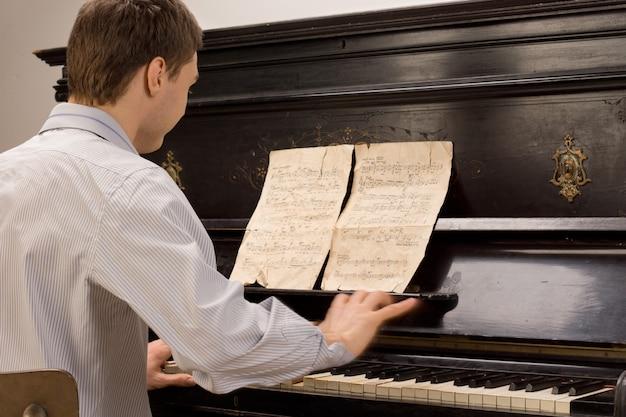 ピアノの練習に座っている若い男性ピアニスト