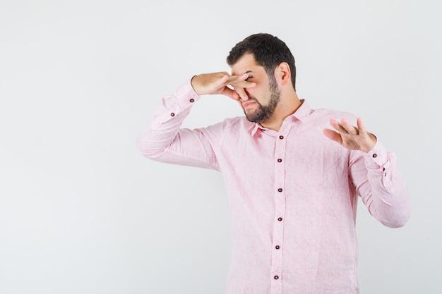 Giovane maschio che si pizzica il naso a causa del cattivo odore in camicia rosa e sembra disgustato