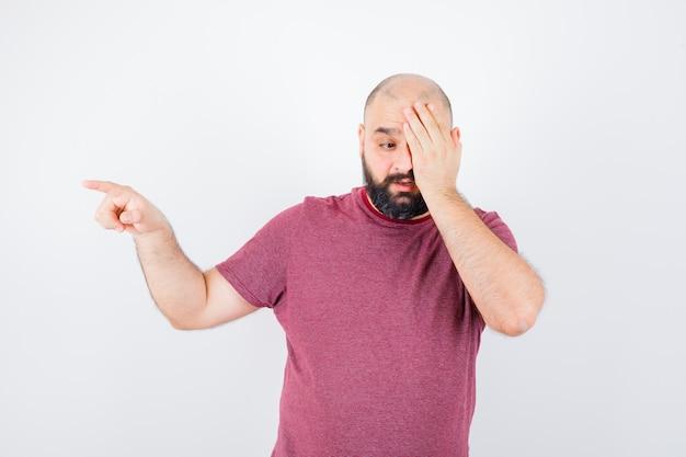 Giovane maschio in maglietta rosa che copre il suo occhio mentre indica da parte e sembra strano, vista frontale.