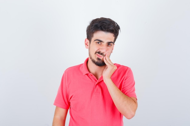 Young male in pink t-shirt having toothache and looking pensive , front view.