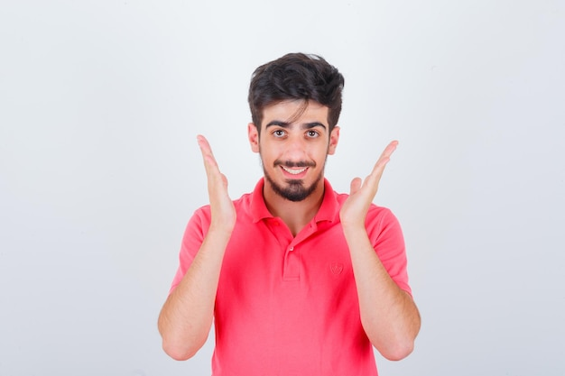 Giovane maschio in maglietta rosa che si tiene per mano vicino alla testa e sembra allegro, vista frontale.
