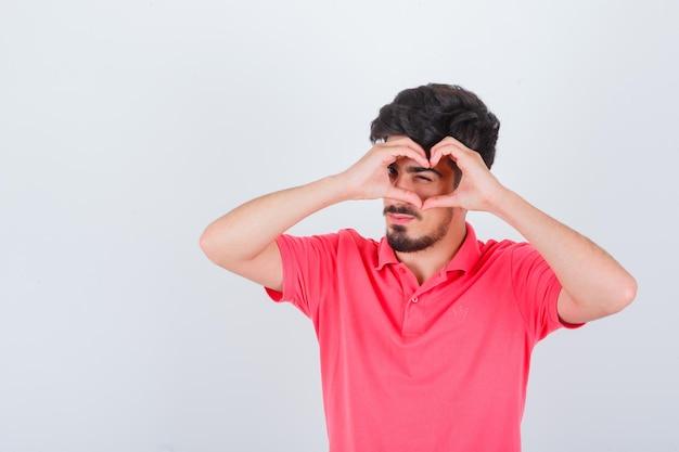 Giovane maschio in maglietta rosa che mostra il gesto del cuore e sembra fiducioso, vista frontale.