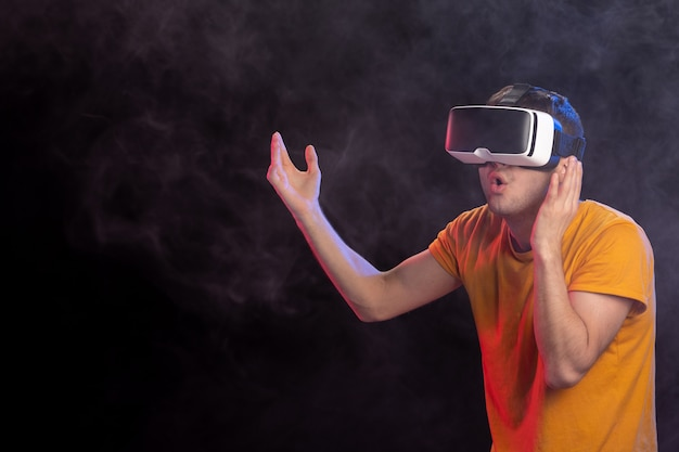 Giovane maschio che gioca gioco spaventoso nella superficie scura di realtà virtuale