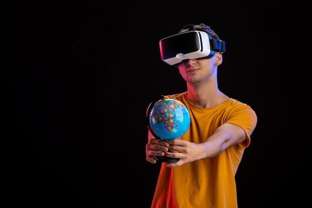 暗い表面に地球儀を保持している仮想現実を再生する若い男性
