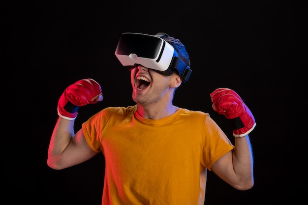 Young male playing virtual reality in mma gloves on dark surface