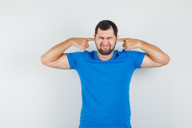 青いtシャツの指で耳を塞いでイライラしている若い男性