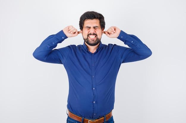 ロイヤルブルーのシャツを着た若い男性が指で耳をふさぎ、長持ちします。正面図。