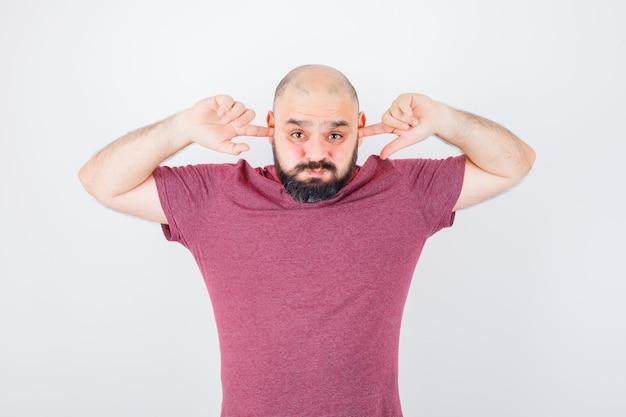 분홍색 티셔츠 전면에서 볼을 부풀리면서 손가락으로 귀를 막는 젊은 남성.