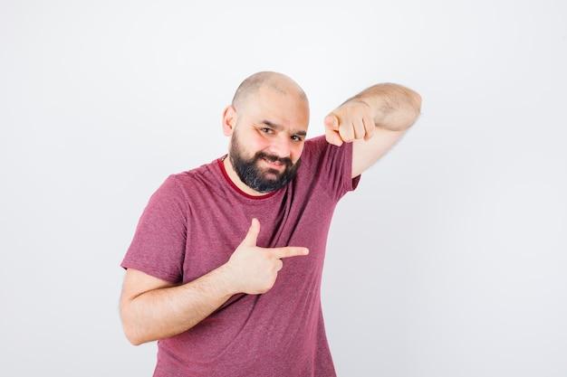 Молодой мужчина указывая в сторону и на камеру в розовой футболке, вид спереди.