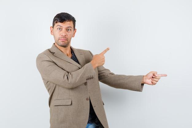若い男性は灰色がかった茶色のジャケットを脇に向けて注意深く見ています。正面図。
