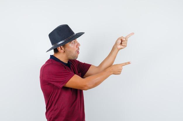 빨간 셔츠, 검은 모자를 옆으로 가리키고 놀란 찾고 있는 젊은 남성. .