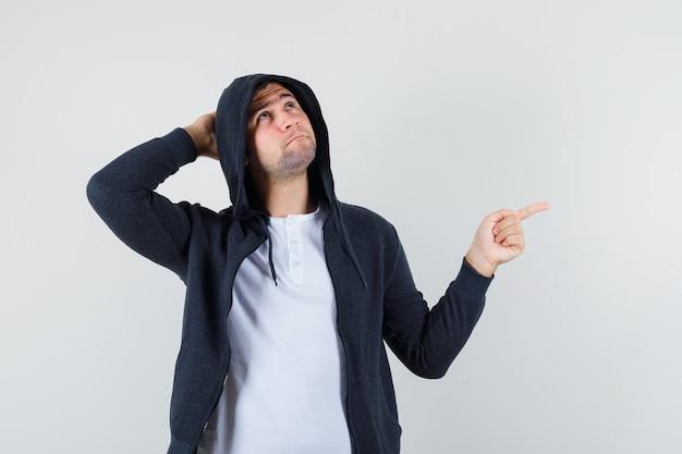 젊은 남성 옆으로 t- 셔츠, 재킷을 가리키고 주저, 전면보기를 찾고.