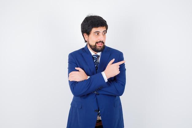 Giovane maschio che indica da parte in camicia, giacca, cravatta e sembra gioioso. vista frontale.