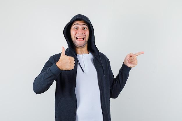 옆으로 가리키는 젊은 남성, t- 셔츠, 재킷에 엄지 손가락을 표시 하 고 기쁜, 전면보기를 찾고.