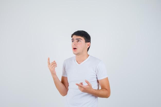 Giovane maschio che indica da parte in maglietta e che sembra perplesso, vista frontale.