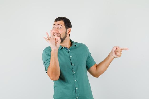 Giovane maschio che indica da parte mentre mostra il gesto ok in camicia verde e sembra soddisfatto. vista frontale.