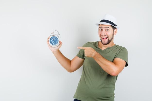 緑のtシャツと帽子の目覚まし時計を指して嬉しそうに見える若い男性