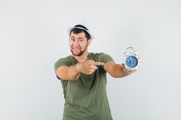 緑のtシャツと帽子の目覚まし時計を指して幸せそうに見える若い男性