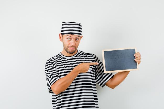 스트라이프 티셔츠 모자에 칠판에서 가리키는 젊은 남성