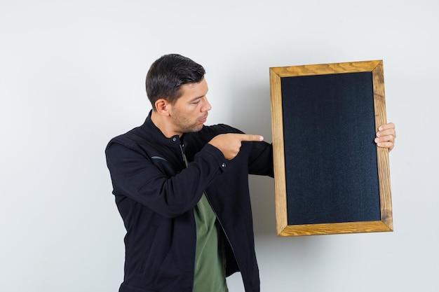 티셔츠, 재킷을 입고 칠판을 가리키고 초점을 맞춘 앞모습을 바라보는 젊은 남성.