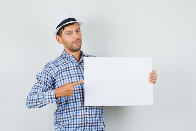 Молодой мужчина указывает на пустой холст в клетчатой рубашке, шляпе и выглядит позитивно