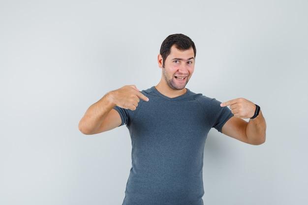 회색 티셔츠에 자신을 가리키고 자랑스러워하는 젊은 남성, 전면보기.