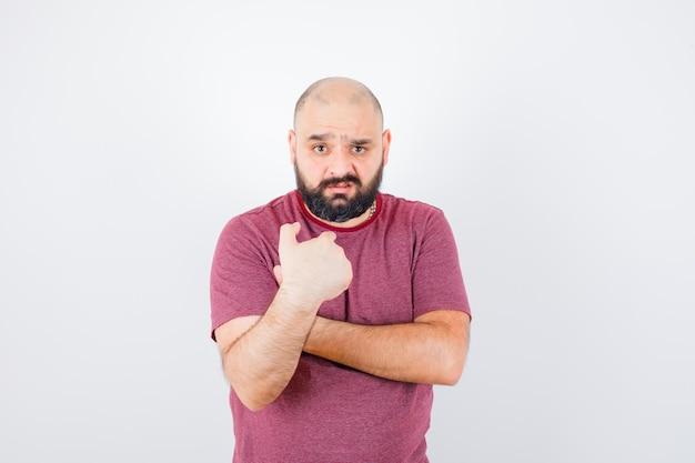 Молодой мужчина указывая на себя в розовой футболке и выглядит смущенным, вид спереди.