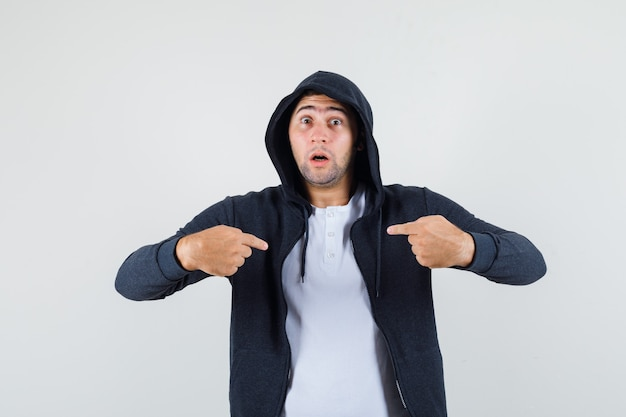 T- 셔츠, 재킷에 자신을 가리키고 의아해 찾고 젊은 남성. 전면보기.