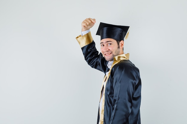 대학원 유니폼에 그의 검은 모자를 가리키고 행복을 찾고 젊은 남성. .