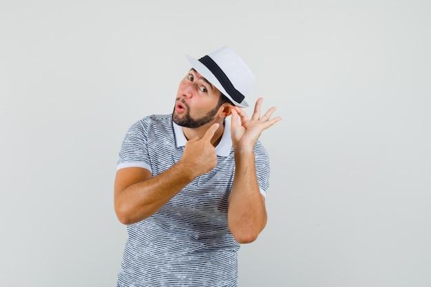 티셔츠, 모자, 정면도에서 그의 귀를 가리키는 젊은 남성.