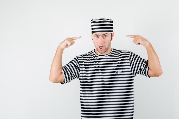 젊은 남성 t- 셔츠, 모자에 그의 머리를 가리키는 자신감, 전면보기를 찾고.