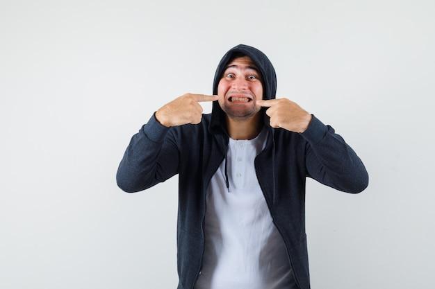 T- 셔츠, 재킷에 그의 이빨을 가리키고 쾌활 한 찾고 젊은 남성. 전면보기.
