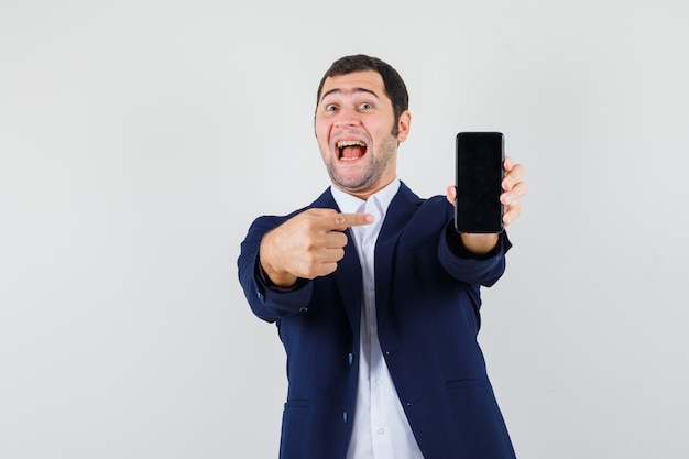 シャツを着て携帯電話を指している若い男性