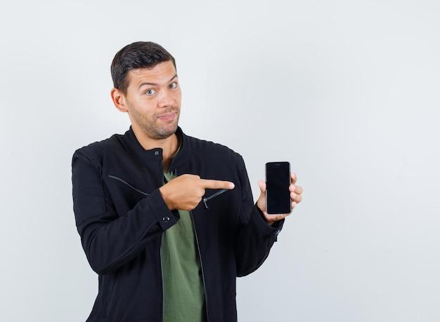 젊은 남성이 티셔츠, 재킷을 입고 휴대폰을 가리키며 쾌활해 보입니다. 전면보기.
