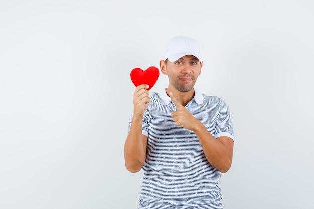 Молодой мужчина указывает на красное сердце в футболке и кепке и выглядит веселым