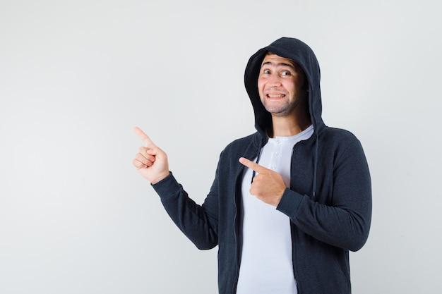 Tシャツ、ジャケット、陽気に見える、正面図で左上隅を指している若い男性。