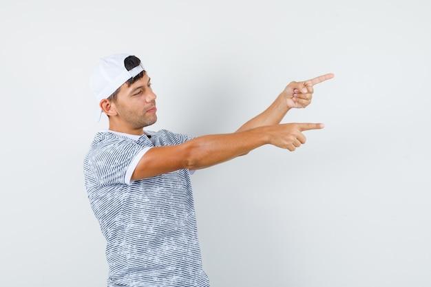 若い男性がtシャツとキャップを指差して希望に満ちている