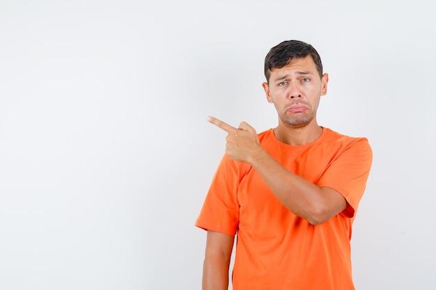 Молодой мужчина в оранжевой футболке указывает в сторону, чтобы пожаловаться, и выглядит обиженным