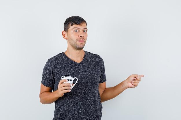 젊은 남성이 검은 티셔츠에 컵을 들고 초점을 맞추며 정면을 바라보면서 다른 곳을 가리키고 있습니다.