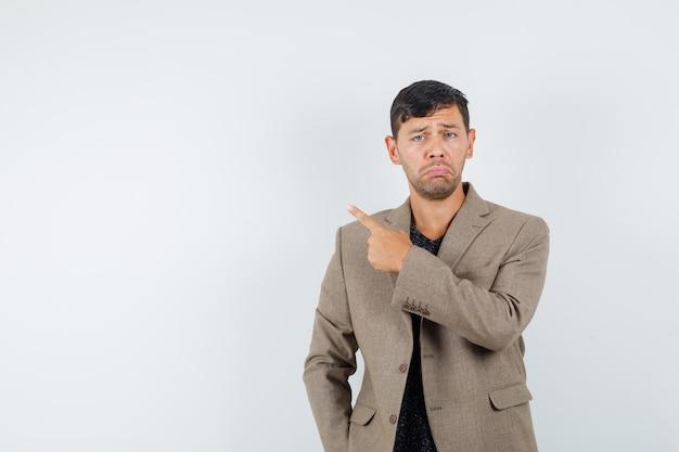 Giovane maschio che punta indietro in giacca marrone grigiastro e sembra deluso, vista frontale. spazio per il testo